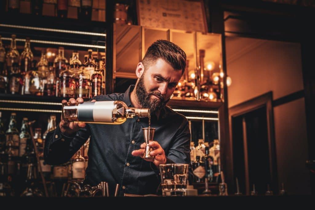 Bartender blandar en drink i baren