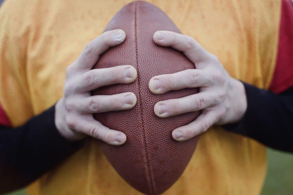 Händer som håller amerikansk fotboll